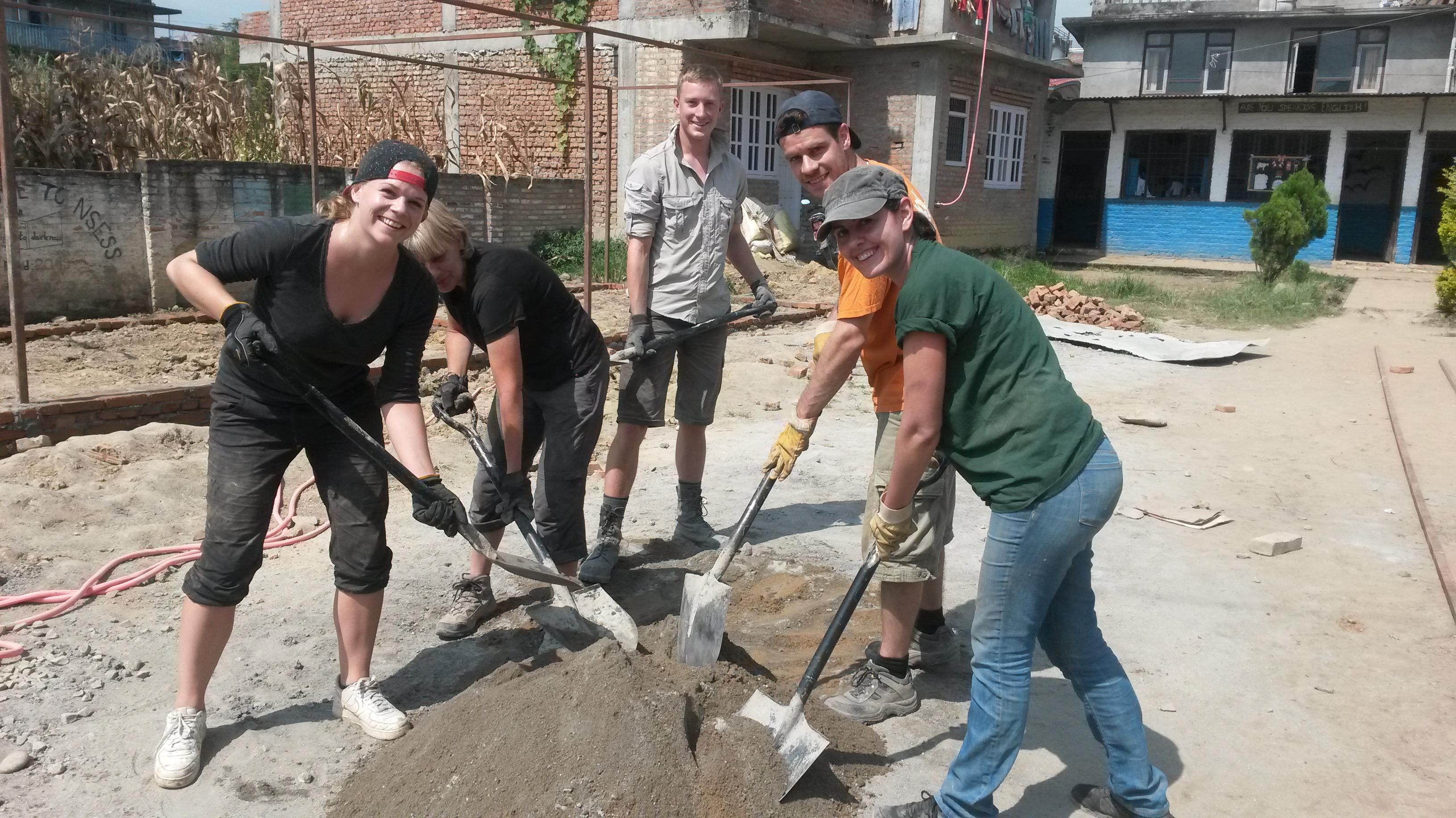 High school student volunteers doing building work in Nepal dig up sand needed for building work.